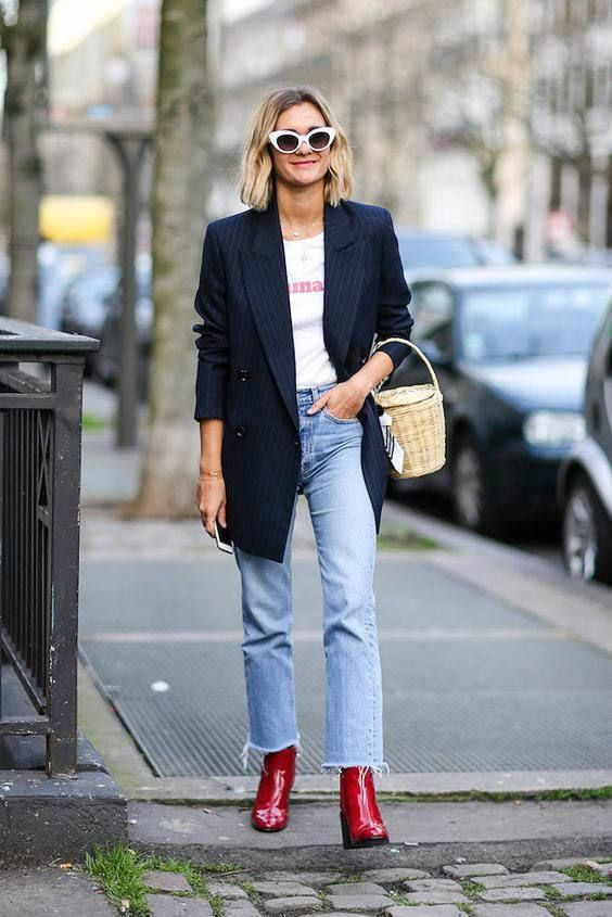 a printed tee, blue jeans with a raw hem, red boots, a navy thin stripe blazer and a basket bag