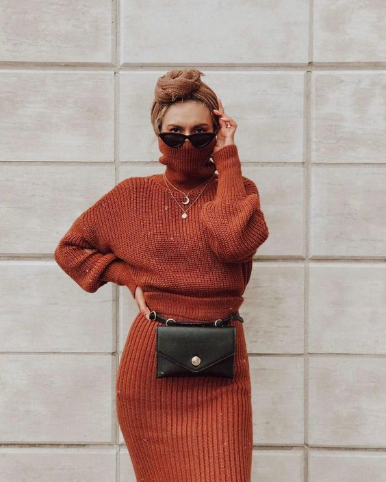 a rust-colored knit suit with a turtleneck sweater, a belt bag and a turban for an edgier look