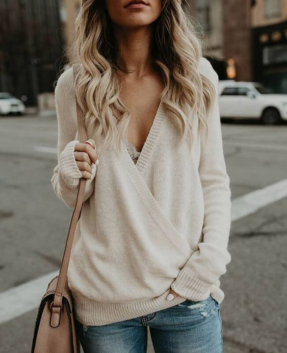 a simple and sexy outfit with blue ripped jeans, a creamy V cut sweater with a lace bralette and a beige bag