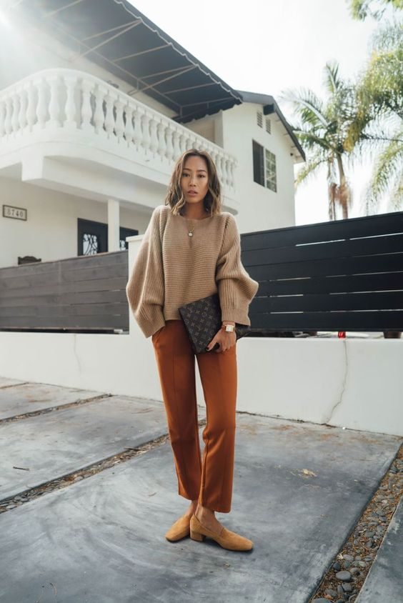 a simple outfit with a tan cropped sweater, rust-colored pants, mustard shoes and a black printed bag