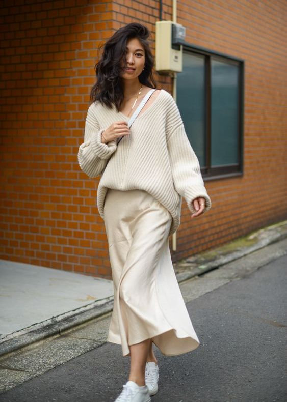 a minimalist monochromatic outfit with a creamy slip midi dress, a ribbed oversized pullover and white sneakers and a bag