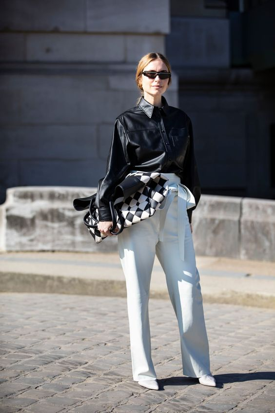 a statement minimalist look with white high waisted pants, a black leather shirt, white shoes and a checked bag