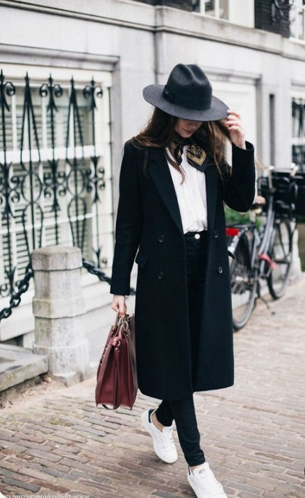 a stylish look with a black straight coat, a black hat and white sneakers looks modern and fresh