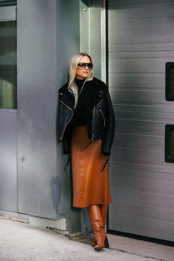 a stylish look with a black turtleneck, an amber leather midi skirt, matching boots and a black aviator coat