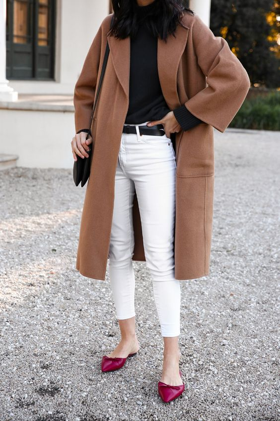 a stylish outfit with cropped white skinnies, a black top, a camel straight knee coat, fuchsia colored slippers