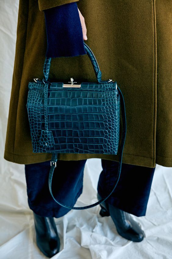 a teal crocodile leather bag with a vintage design will give a refined feel to your look