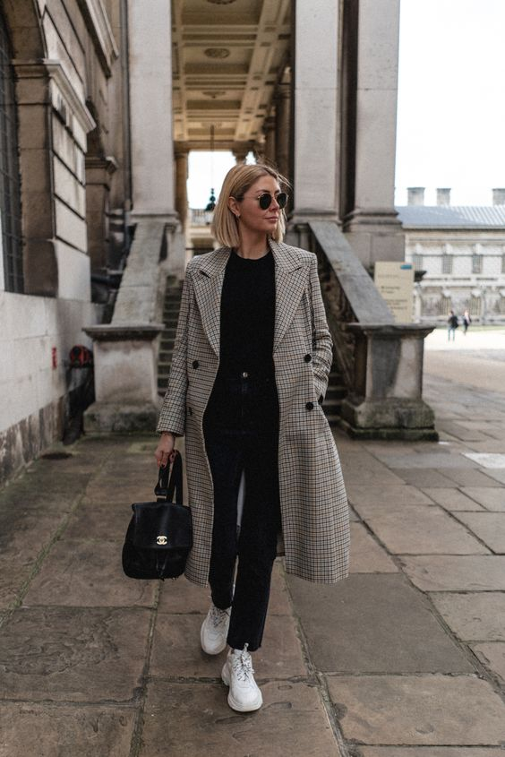 a casual look with black jeans, a black top, white trainers, a black backpack and a printed straight midi coat