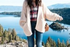 16 a travel outfit with a plaid shirt, a creamy chunky knit cardigan, blue jeans, brown boots and a bag