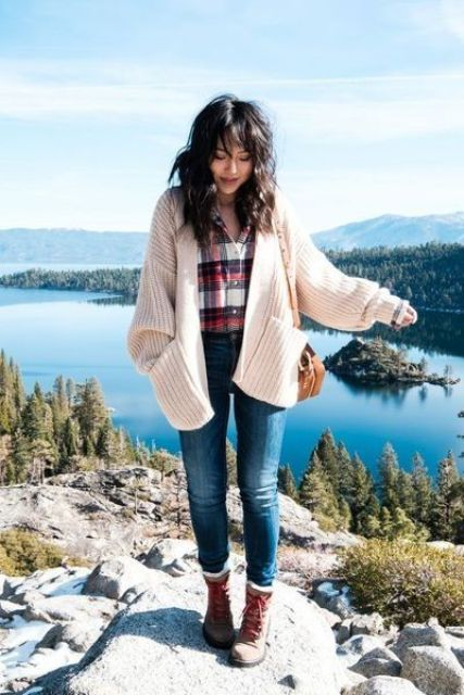 a travel outfit with a plaid shirt, a creamy chunky knit cardigan, blue jeans, brown boots and a bag