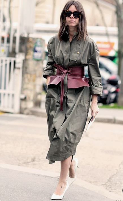 an olive green midi shirtdress with long sleeves, a burgundy corset belt and white shoes