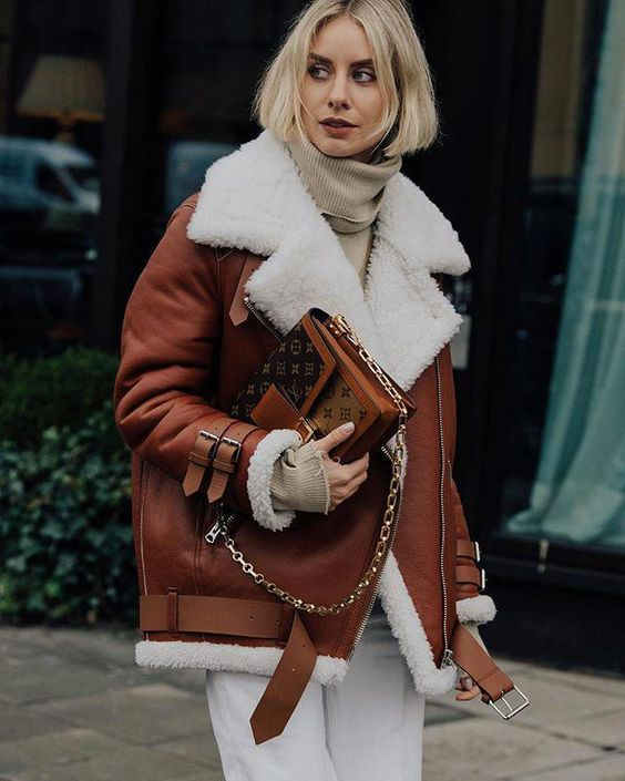 an oversized beige sweater, white straight pants, an oversized brown and white aviator coat