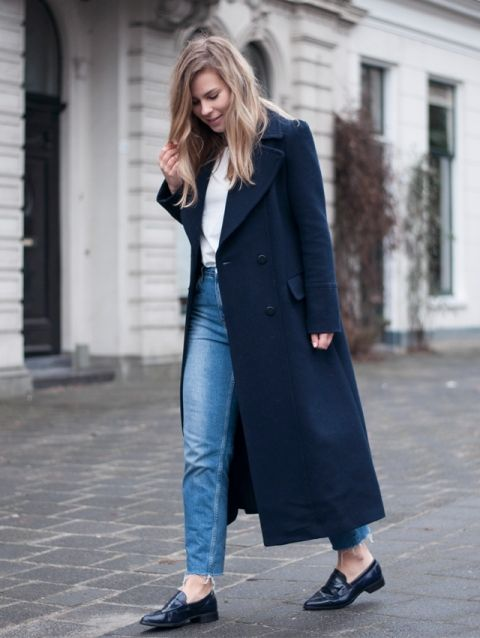 a casual outfit with a white top, blue jeans, navy loafers and a navy straight coat for more comfort
