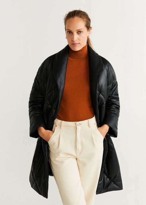 a minimalist look with creamy pants, a rust-colored turtleneck, a black leather midi padded coat