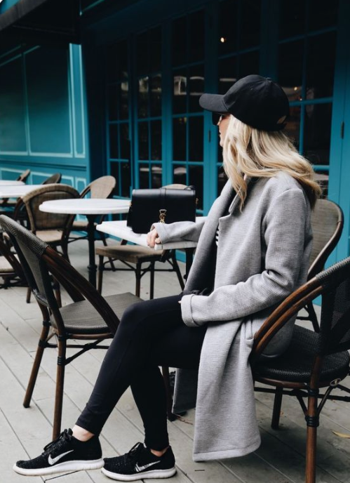 a monochromatic outfit with a grey coat, black sneakers and a black cap combines sport and casual