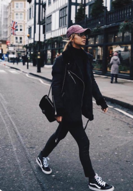 a black aviator coat, black trainers and a pink cap make up a very bold and edgy outift for winter