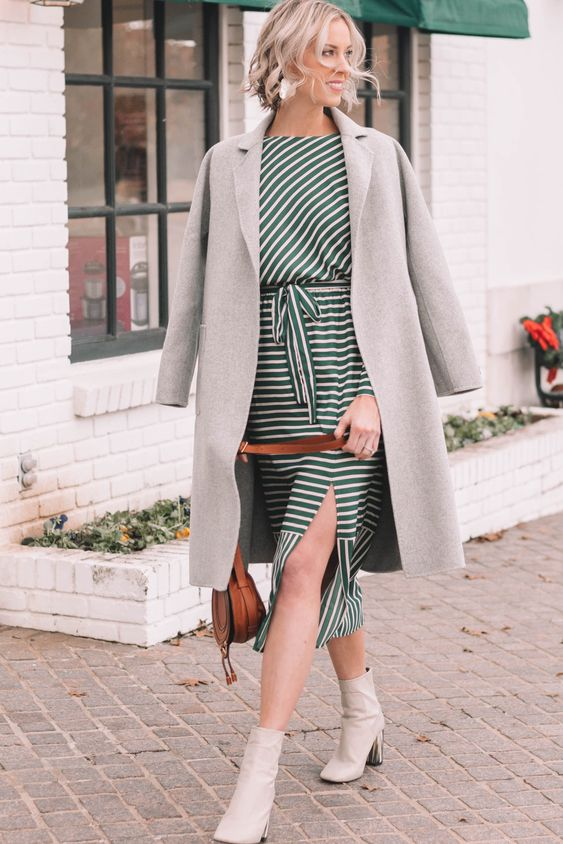 a girlish outfit with a striped midi dress with a slit, white booties, a grey straight coat and a brown bag