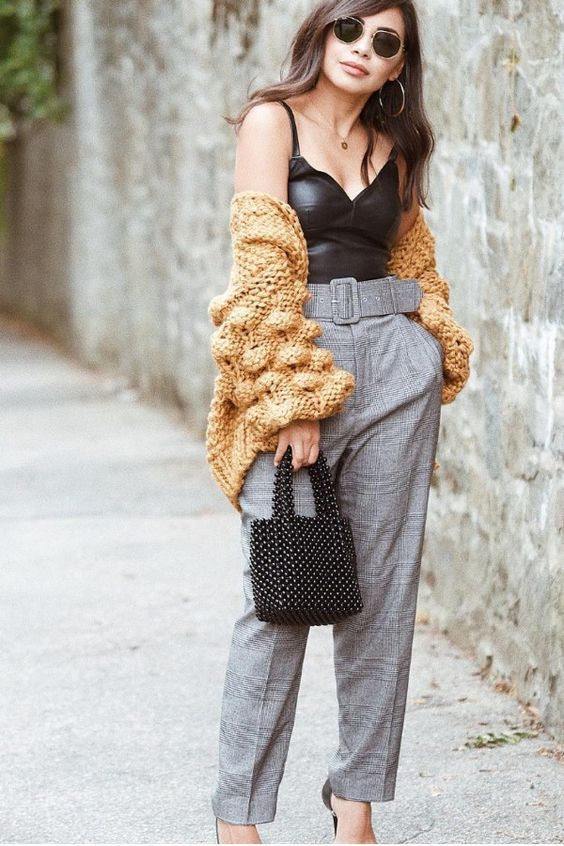 a sexy outfit with a black leather top, grey plaid pants, a yellow cunky knit cardigan and heels