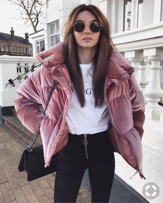 a stylish look with a white printed tee, black skinnies, a pink velvet padded coat and a black bag