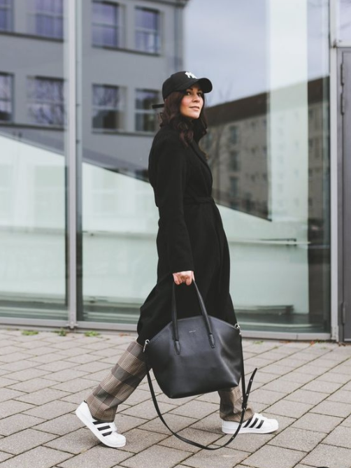 a black coat, white sneakers and a black cap make up a bold yet casual enough outfit for the winter