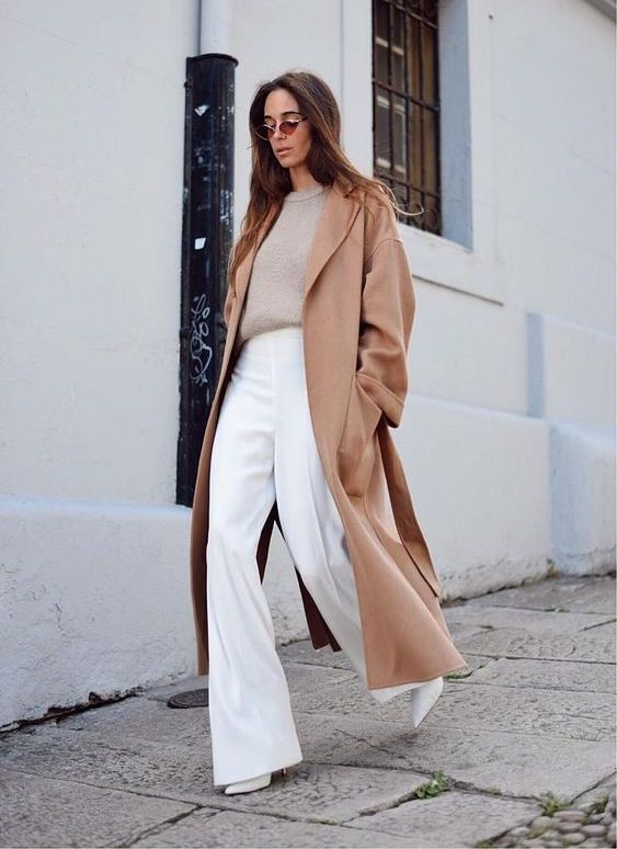 a minimalist look with a neutral cashmere top, white wideleg pants, white boots and a camel straight coat