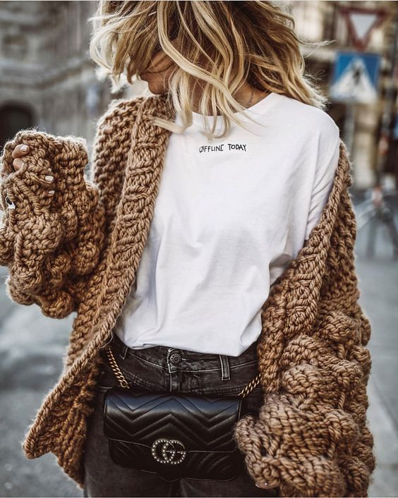 grey jeans, a white printed tee, an oversized brown cardigan and a waist bag for a bit of trend
