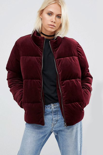 a 90s inspired look with blue straight jeansm a black tee, a burgundy velvet padded jacket