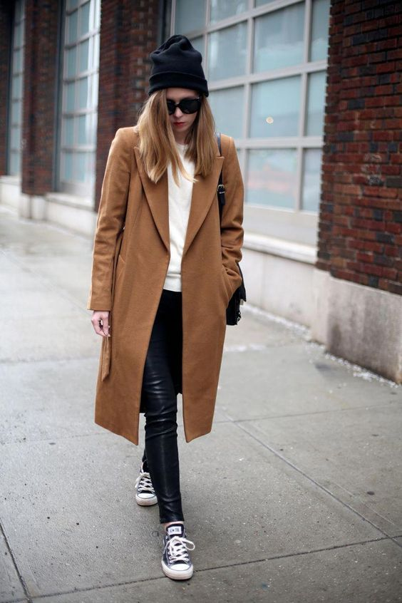 a casual winter look with a white top, black leather leggings, black sneakers, a camel straight coat, a black bag and a black beanie