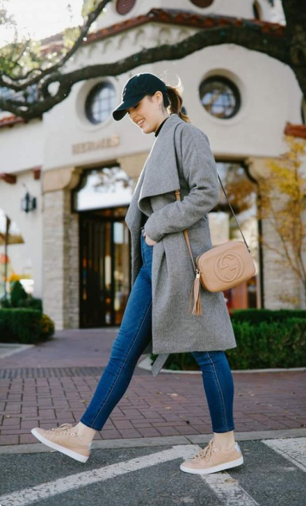 a grey coat, peachy sneakers and a black cap for a stylish and a bit sporty look for the fall