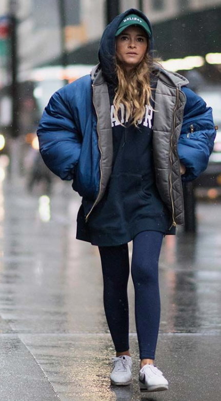 a sport look with a padded coat, white sneakers and a cap - all about comfort this winter