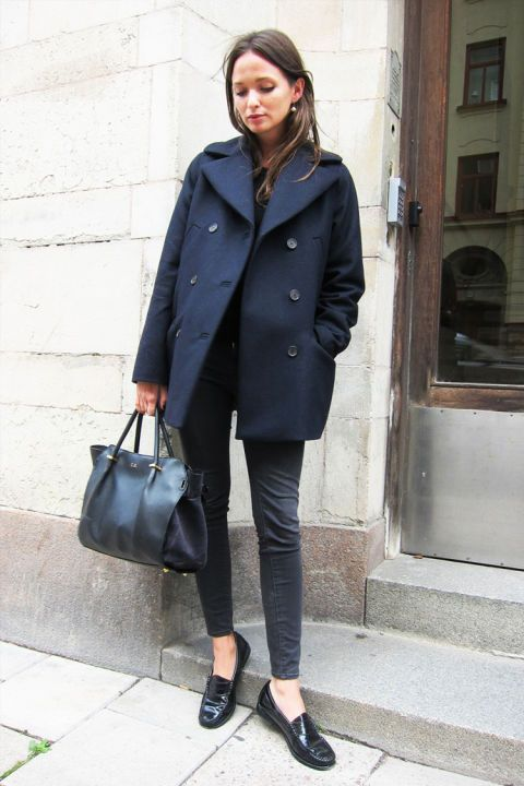 an elegant casual outfit with graphite grey jeans, blakc loafers, a black top, a navy pea coat and a black bag