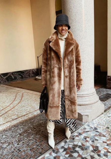 a trendy look with a camel faux fur coat, white boots and a black bucket hat for winter