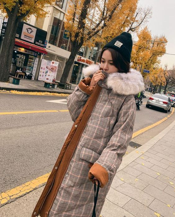 a padded midi coat that imitates plaid tweed and is decorated with neutral faux fur