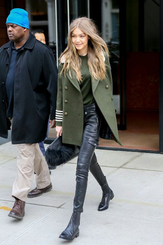 Gigi Hadid wearing black leather pants, a green top, black boots, a grene pea coat and a bag