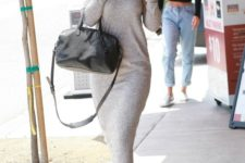 Gigi Hadid wearing a grey knit midi dress with long sleeves, a high neckline and a black bag and white sneakers