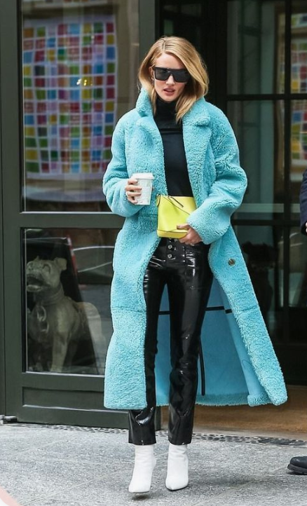 Rosie Huntington Whiteley wearing black lacquer pants, a black turtleneck, white boots and a turquoise midi faux fur coat