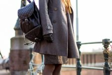 With beret, black backpack, gray coat and black lace up boots