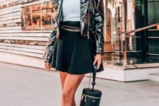 With black cap, white top, black mini skirt, unique bag and boots