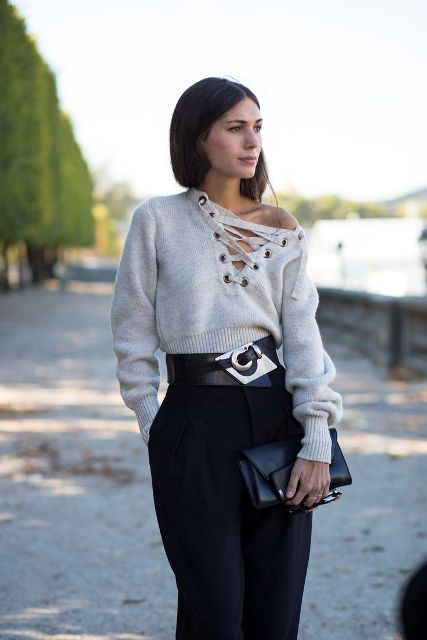 With black high-waisted trousers, black leather clutch and embellished belt