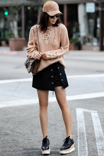 With black lace up mini skirt, platform shoes, printed bag and cap