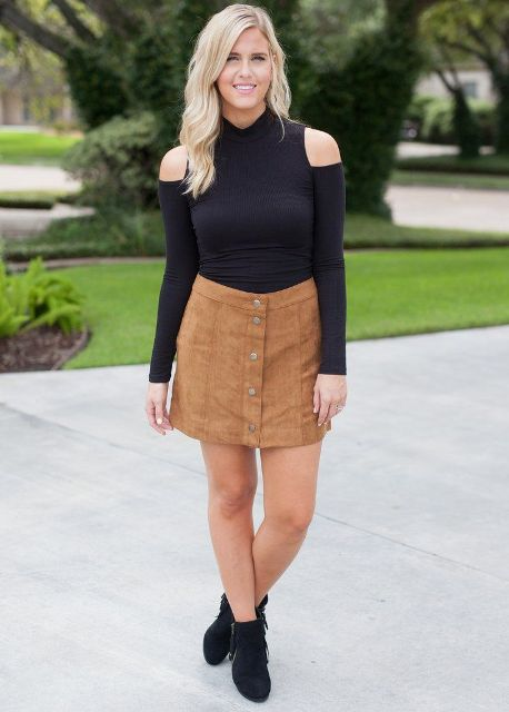With black off the shoulder shirt and black ankle boots