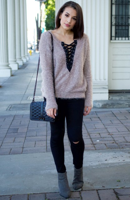 With black pants, gray ankle boots and chain strap bag