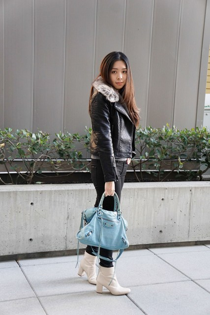 With black pants, white ankle boots and light blue bag