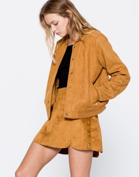 With black shirt and brown suede mini skirt