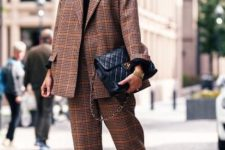 With black shirt, checked cropped pants, black leather bag and fur shoes