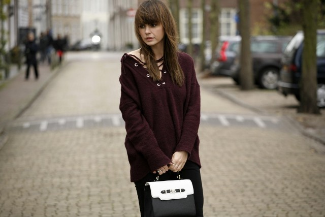 With black straight pants and black and white bag