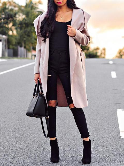 With black top, distressed pants, ankle boots and black bag