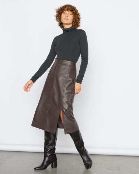With black turtleneck and black leather high boots