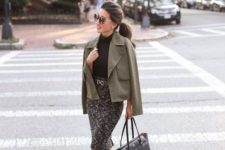 With black turtleneck, olive green jacket, black tote bag and black ankle strap high heels