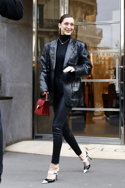 With black turtleneck, red bag, leather skinny pants and white and black high heels