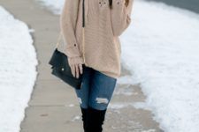 With distressed jeans, black over the knee boots and chain strap bag